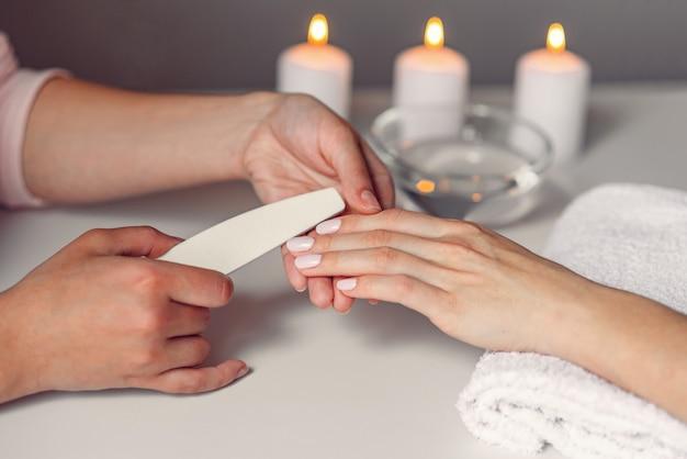 Mani di bella donna che hanno limatura delle unghie con lima per unghie dal manicure. procedura cosmetica, manicure sulla mano femminile