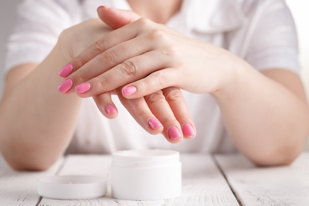 Mani di donna bella con crema