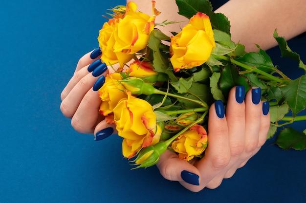 Bella donna mani con manicure tenendo le rose contro il classico sfondo blu