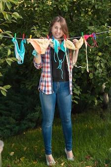 Bella donna che appende i costumi da bagno su stendibiancheria in giardino