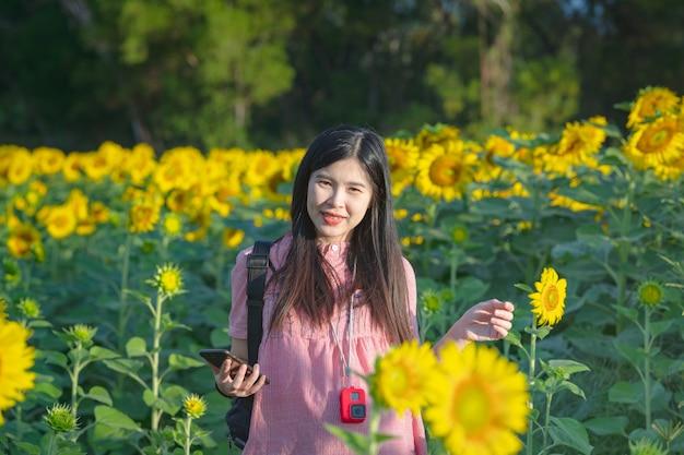 La bella donna felice e gode nel campo del girasole