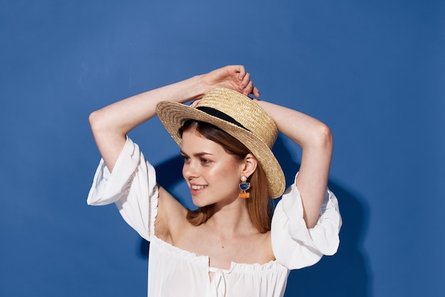 Bella donna in cappello decorazione fascino closeup sfondo blu. foto di alta qualità