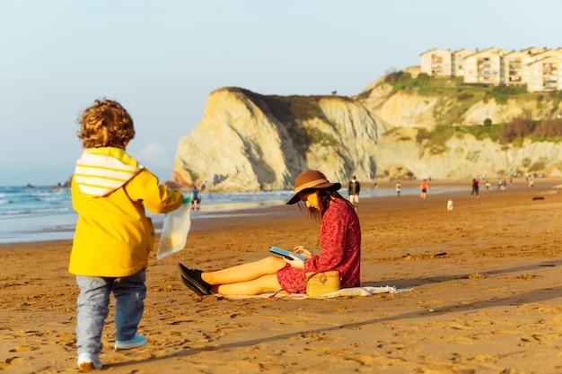 Bella donna con cappello e vestito rosso che controlla la posta dal lavoro sulla spiaggia