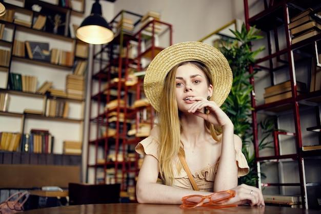Bella donna in un cappello seduto a un tavolo in un caffè vacanza libro divertente.