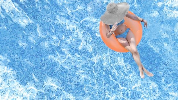 Bella donna in cappello in piscina vista aerea dall'alto dall'alto