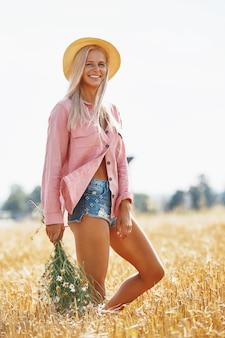 Bella donna in cappello e con un cesto di margherite di campo nella soleggiata giornata estiva.