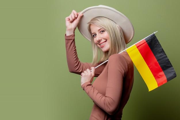 Bella donna in un cappello con la bandiera della germania