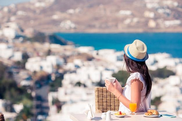 Bella donna facendo colazione al bar all'aperto con vista mozzafiato.