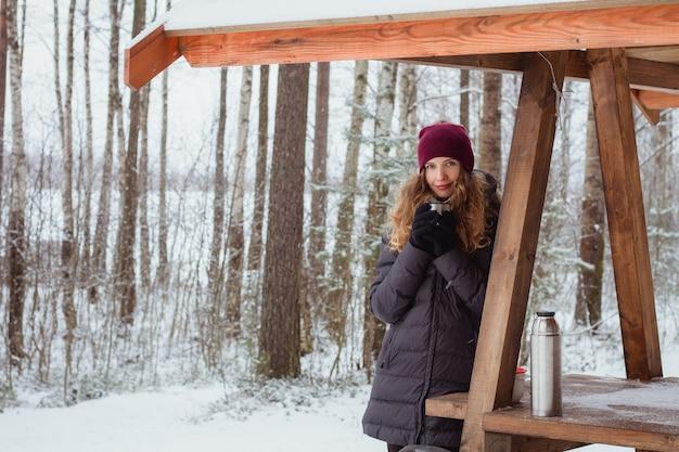 La bella donna che beve una bevanda calda da un thermos sul campeggio turistico nella foresta invernale