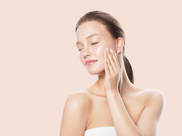 Il ritratto sano di concetto di cura della pelle della bella donna con le mani si chiude su fondo beige. foto in studio studio