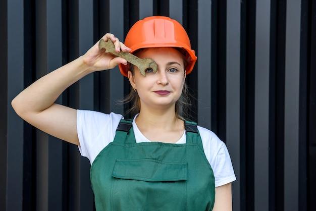 Bella donna in casco e tuta che tiene la chiave di fissaggio sopra l'occhio