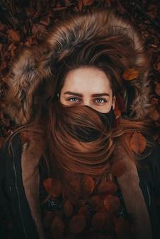 Bella donna che tiene le foglie autunnali con la maschera facciale