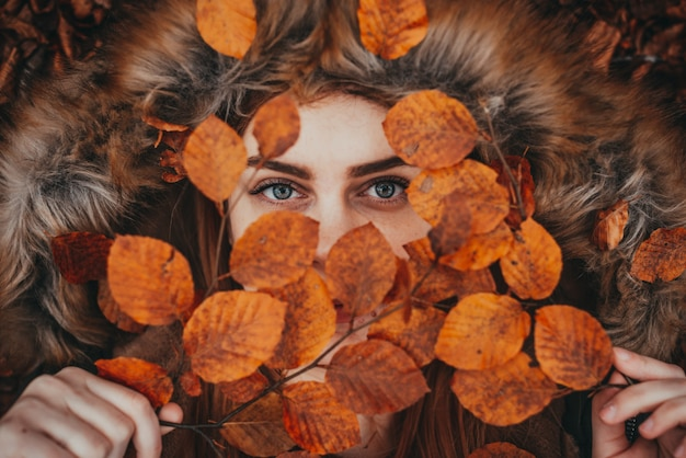 Bella donna che tiene le foglie d'autunno