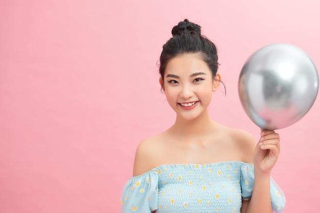 Bella donna con palloncino su sfondo rosa