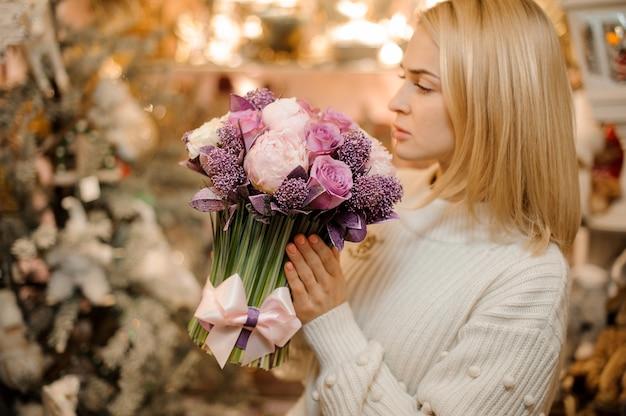 Bella donna che tiene un bouquet di teneri fiori di colore rosa e viola con steli verdi