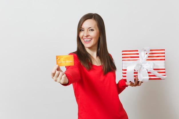 Bella donna che tiene la carta di credito, scatola regalo rossa con regalo isolato su sfondo bianco. per la pubblicità. san valentino, giornata internazionale della donna, natale, compleanno, concetto di vacanza.