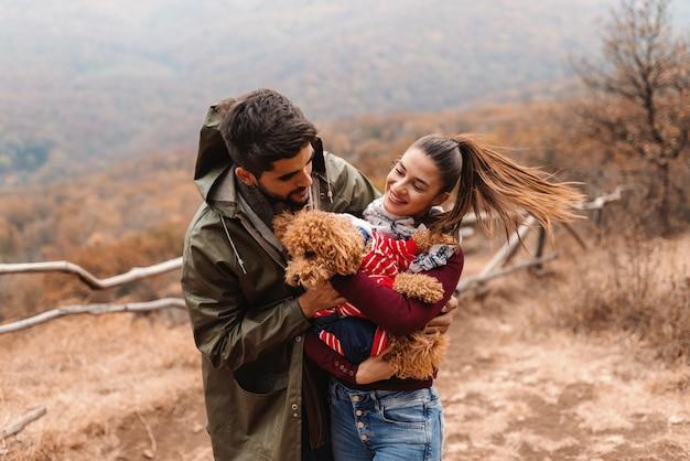 Cane della holding della bella donna mentre uomo che lo coccola.