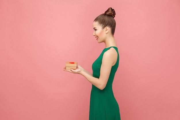 Bella donna che tiene in mano una confezione regalo con cuori sorridenti a trentadue denti