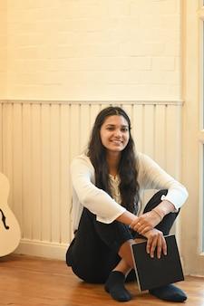 Bella donna che tiene un taccuino in sue mani mentre sedendosi sul pavimento di legno sopra la stanza di rilassamento della scuola di musica come fondo.