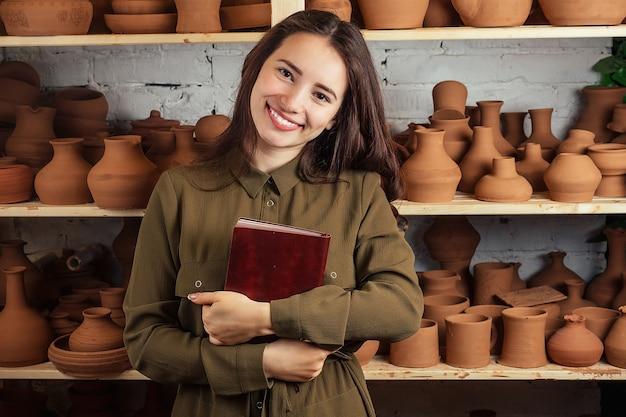 Bella donna che tiene un taccuino in un laboratorio di ceramica. il vasaio scrive idee su uno sfondo di un rack con pentole e vasi di terracotta. il concetto di ispirazione e business.