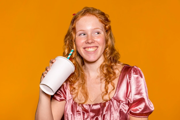 Bella donna che tiene un bicchiere di carta