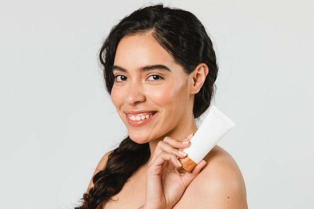 Bella donna che tiene un prodotto per la cura della pelle skin