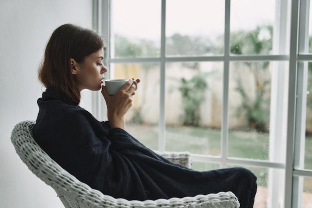 Bella donna a casa con una tazza di una bevanda calda