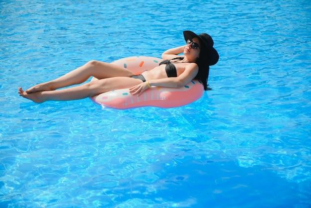 Bella donna e anello gonfiabile da bagno a forma di ciambella in piscina