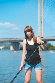 Una bella donna è impegnata in sport attivi estivi sul fiume su una tavola sup