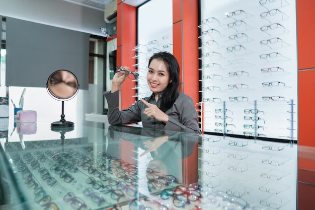 Una bella donna è in posa tenendo gli occhiali sullo sfondo di una vetrina di occhiali in una clinica oculistica