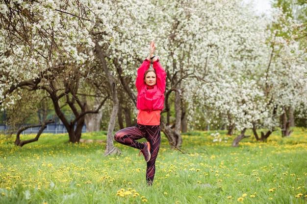 La bella donna sta praticando l'yoga all'aperto nel parco in primavera.