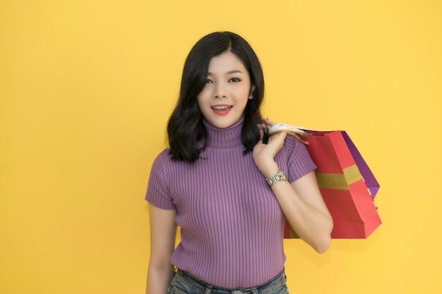 La bella donna sta comperando nel centro commerciale facendo uso della carta di credito i vetri d'uso della donna e la tenuta del sacchetto della spesa adattano nel grande magazzino.