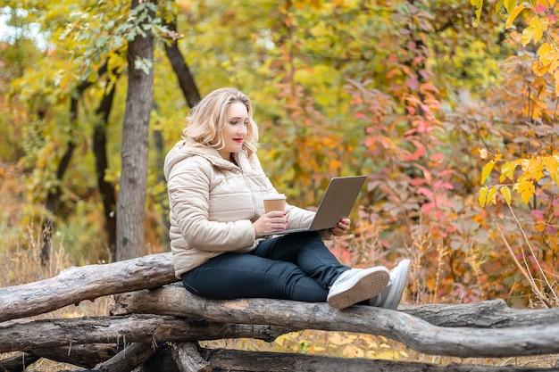 Una bella donna è seduta in un parco autunnale davanti a un laptop e tiene in mano un bicchiere di caffè