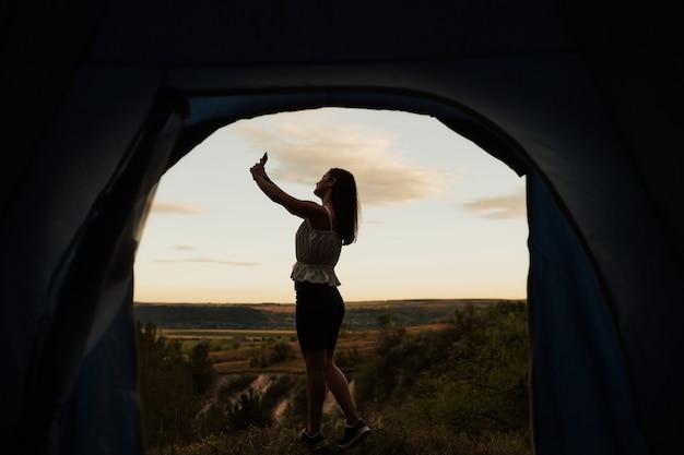 Bella donna sta prendendo un selfie al mattino con il suo telefono cellulare vicino alla tenda con una montagna come sfondo.