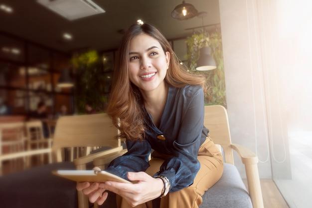 La bella donna sta lavorando con la compressa in caffetteria