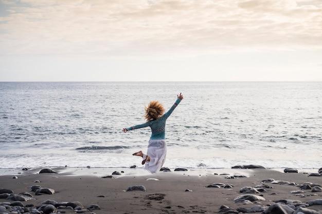 La bella donna salta per il successo e gioiosa in spiaggia di fronte alla natura e all'oceano. vibrazioni positive estive in una spiaggia di pietre nere a tenerife. vincitore e concetto di felicità