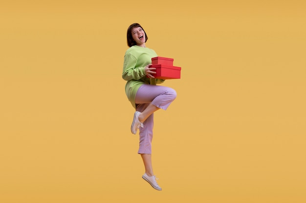 Bella donna che salta isolato sull'arancio