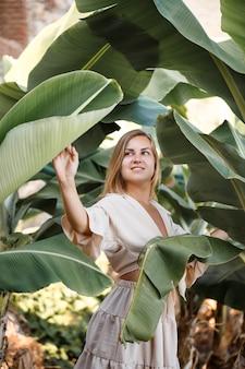 Bella donna nella giungla. un resort o un hotel con alberi e piante tropicali. donna con foglia di banana vicino. ragazza in vacanza nella foresta pluviale