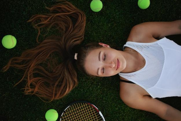 Bella donna sdraiata sul campo da tennis in erba con palline da tennis intorno a lei, vista dall'alto