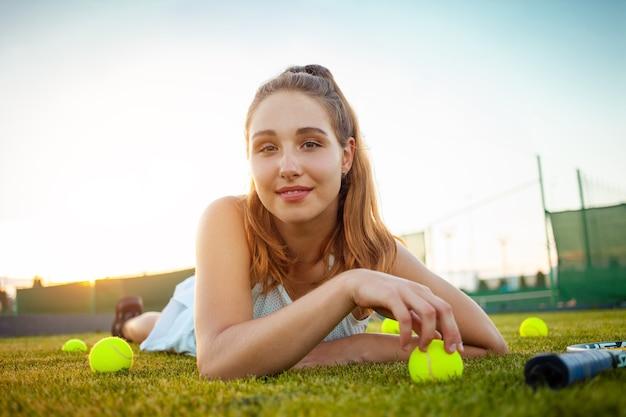 Bella donna sdraiata sul campo da tennis in erba con palline da tennis intorno a lei