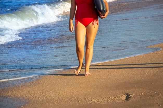 Belle gambe della donna, camminando sulla spiaggia