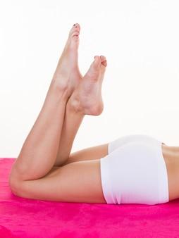 Belle gambe della donna su bianco