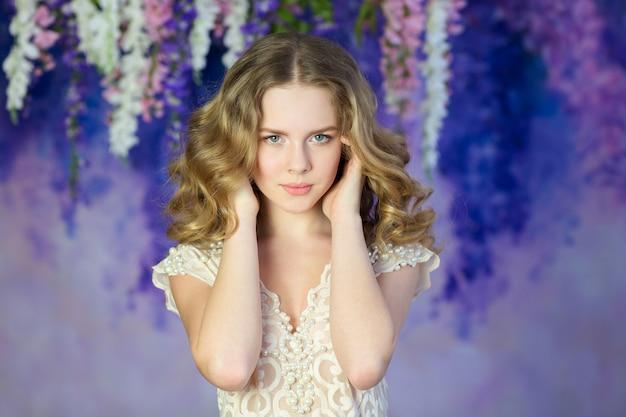 Bella donna in un abito leggero in posa su arbusti fioriti.