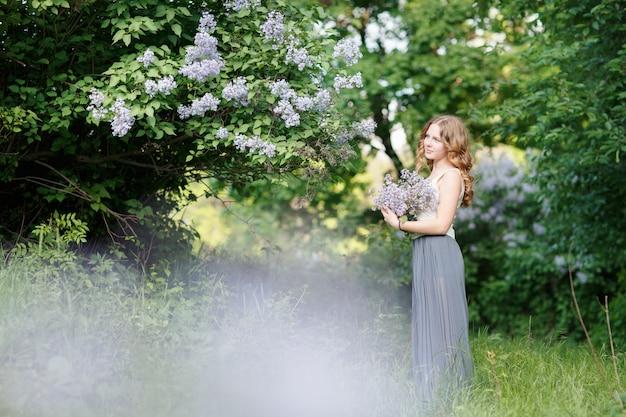 Bella donna in un abito leggero in posa con arbusti fioriti.