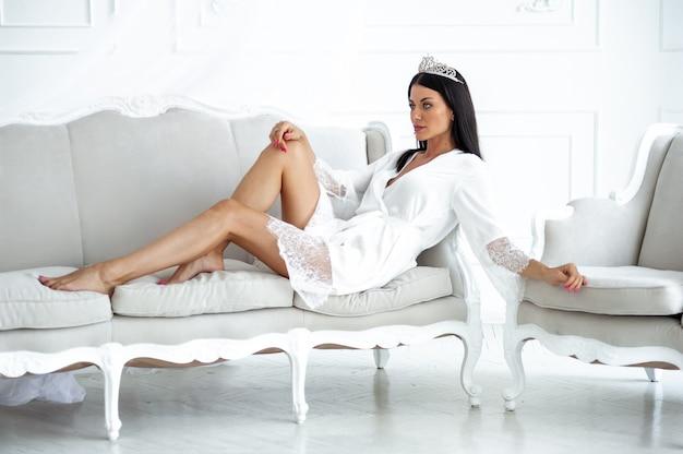 Bella donna in abito bianco chiaro con corona come la regina