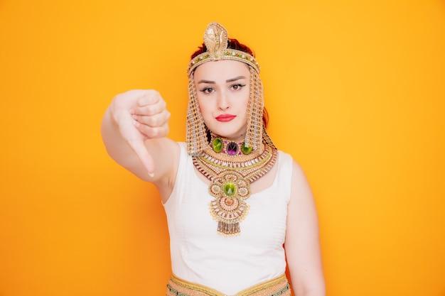 Bella donna come cleopatra in antico costume egiziano dispiaciuta che mostra il pollice in giù sull'arancia