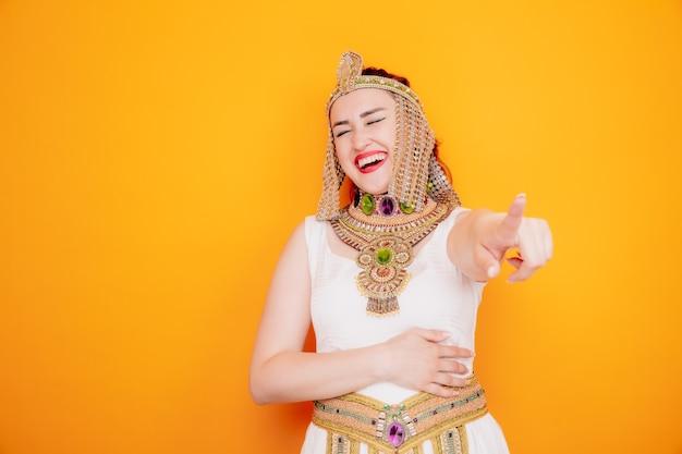 Bella donna come cleopatra in antico costume egiziano che punta con il dito indice che ride sull'arancia