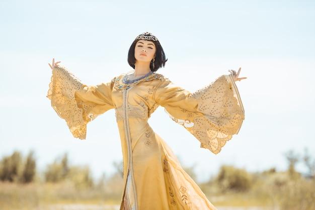 Bella donna come la regina egiziana cleopatra nel deserto all'aperto
