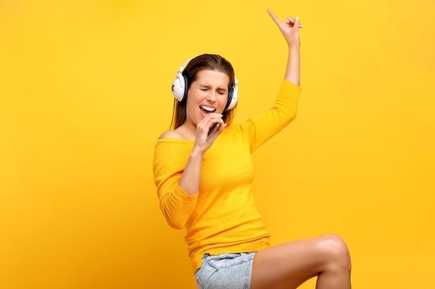 Bella donna che ascolta la musica sul telefono cellulare sopra il giallo