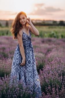 Bella donna in un abito lungo in un campo di lavanda al tramonto.